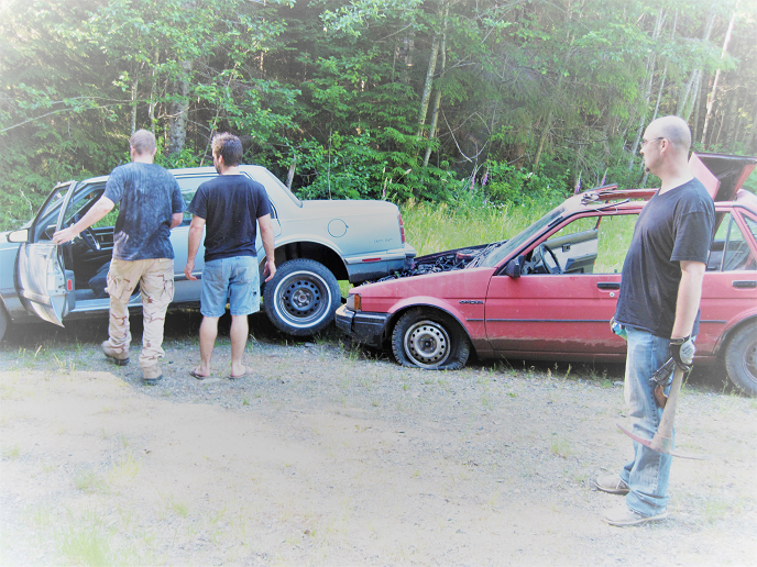 Three men looking at two wrecked cars during mancation getaway