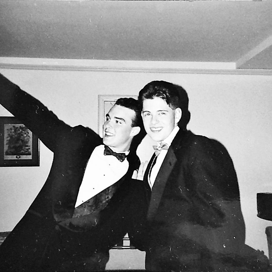 Two men posing for photo wearing tuxedos